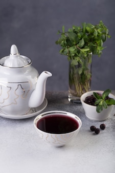 Freshly brewed tea is poured into a bowl, next to it is a chocolate cake decorated with a sprig of fresh herbs