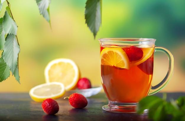 Свежезаваренный чай с лимоном и клубникой в большой стеклянной чашке
