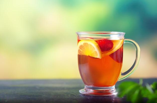 Свежезаваренный чай с лимоном и клубникой в большой стеклянной чашке Premium Фотографии