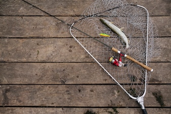Freshly caught fish inside the fishing net with fishing rod over the wooden pier