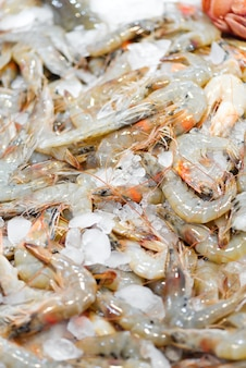 Свежевыловленные натуральные сырые сырые креветки на льду на рынке. морские деликатесы.