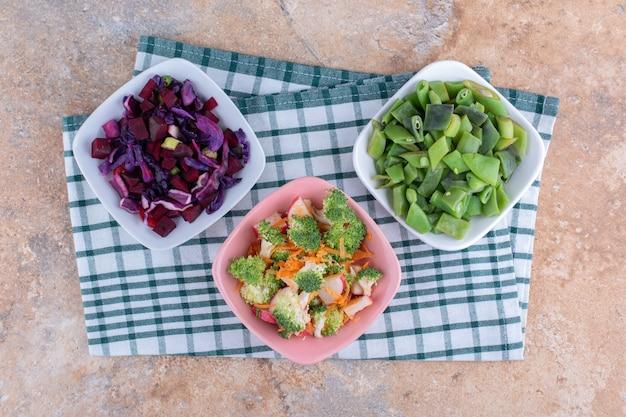 Свежие нарезанные овощи смешать и сложить в миски на мраморной поверхности.