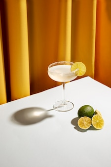 Freshly cocktail drink with salty rim and lemon slices over white desk