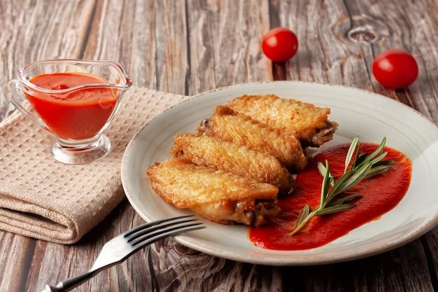 Свежеприготовленные крылья буйвола крупным планом с томатным соусом и помидорами