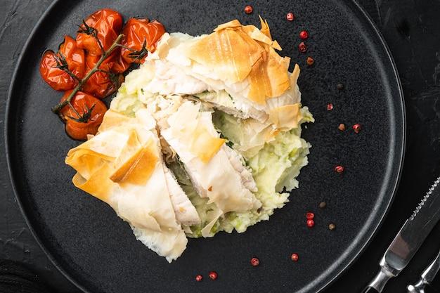 Свежеприготовленная курица по-киевски с сочным чесноком и маслом петрушки, с запеченными помидорами черри, картофельным пюре, на черном каменном столе, плоская планировка, вид сверху
