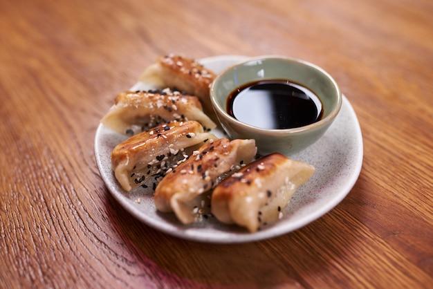 焼きたて餃子ゲッツァ醤油。木製の背景に