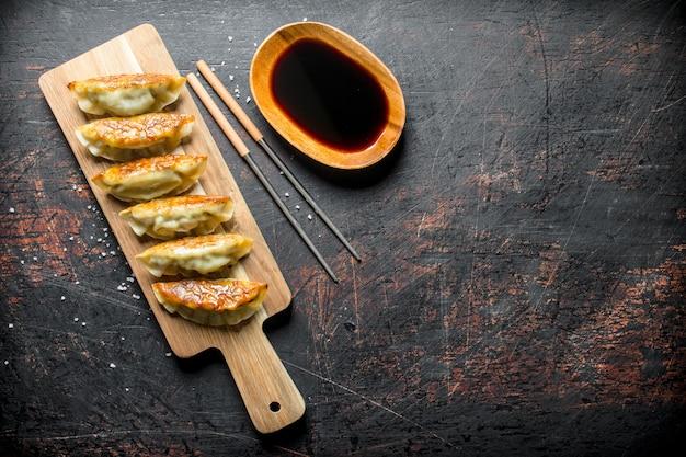 Freshly cooked dumplings gedza with soy sauce.