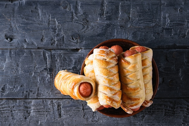 Freshly cooked homemade sausage rolls in a clay bowl on a dark wooden table.