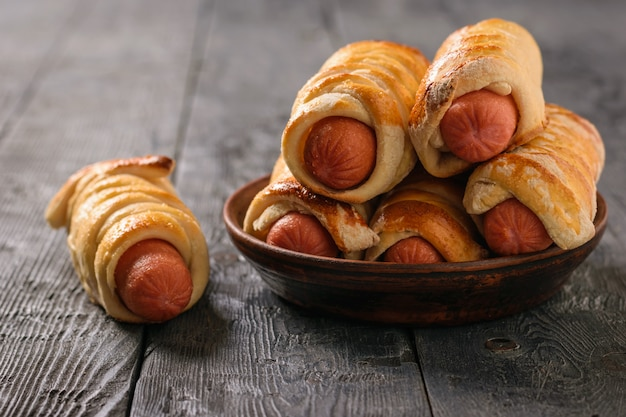 Freshly cooked homemade sausage rolls in a clay bowl on a rustic wooden table.