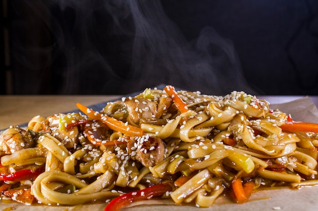 Freshly cooked hot udon noodles with chicken and vegetables on a table