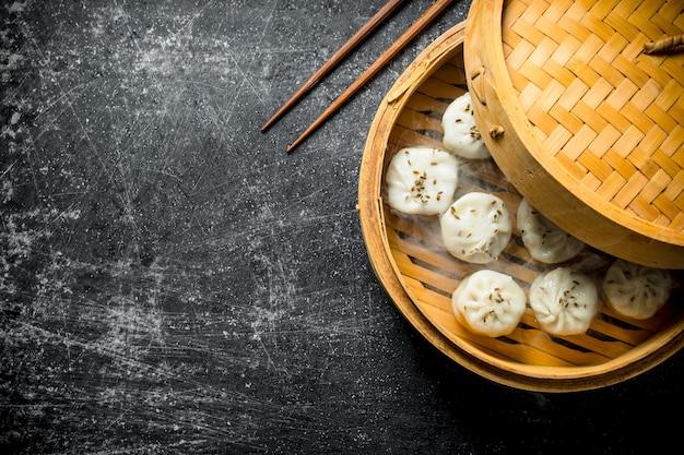 Freshly cooked manta dumplings in a bamboo steamer. on dark rustic background