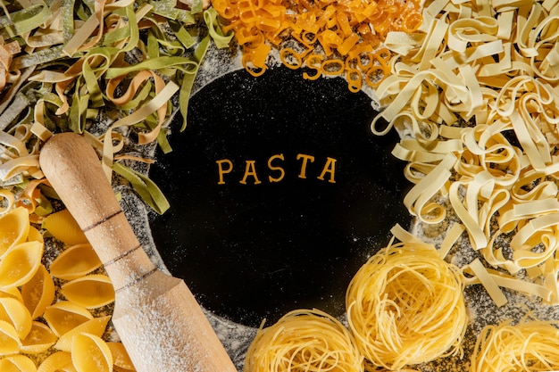 Freshly cooked pasta is lying on a dark surface dusted with flour. italian pasta. tagliatelle. raw pasta. italian pasta recipe. top view, copy space.