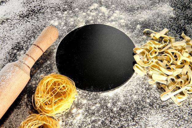 小麦粉をまぶした暗い表面に、作りたてのパスタが横たわっています。 ce。