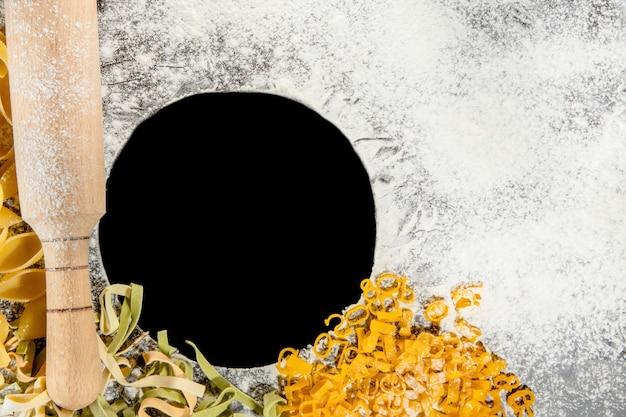 Свежеприготовленные макароны лежат на темной поверхности, присыпанной мукой. итальянская паста. тальятелле. сырая паста. рецепт итальянской пасты. вид сверху, копировать пространство