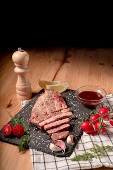 Свежеприготовленный стейк из свинины на грифельной доске, с солью, черным перцем, чесноком, вишней, помидорами, зеленью и лимоном .. вертикаль