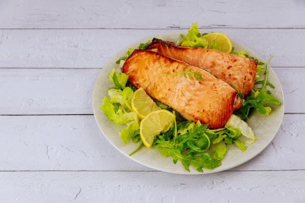 Freshly cooked salmon in plate with salad and lemon on white wooden table.