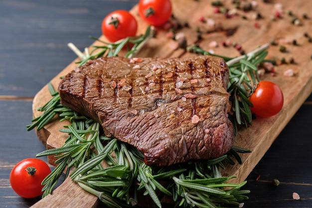 Свежеприготовленный стейк на ветках розмарина. блюдо подается на большой деревянной доске с помидорами черри