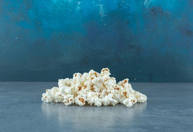 Свежеприготовление кучи хрустящего попкорна на синем фоне. фото высокого качества