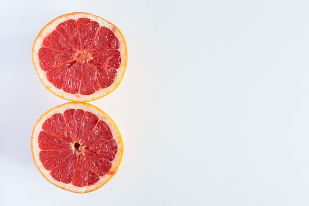 Freshly cut grapefruit in half on a white background