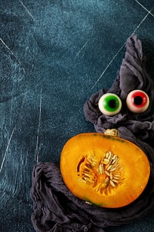 Freshly cut in half pumpkin with gray napkin and halloween decorations with eyes on old stone dark blue