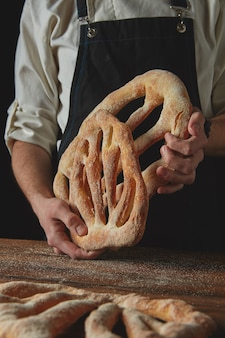 Freshly delicious bread baker holds in hands on a dark background
