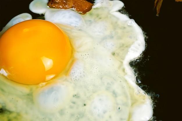 Свежеобжаренное яйцо на сковороде с кусочками свиного сала или бекона для сбалансированного питания на домашней кухне. английский или американский завтрак. крупный план. в помещении.