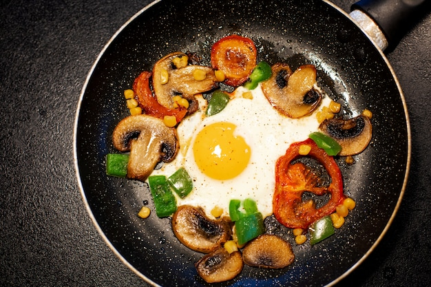 Freshly fried eggs with vegetables in a pan