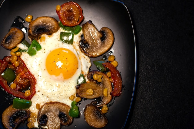 Freshly fried scrambled eggs with vegetables on a black plate