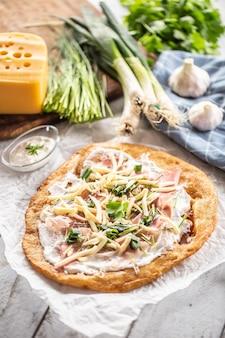 Свежие венгерские ланго, поданные на бумаге для выпечки, со сливками, сыром, ветчиной прошуитто, чесноком и луком.