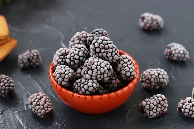 暗い背景のボウルに新鮮な冷凍ブラックベリー、冬の冷凍ベリー、水平配置