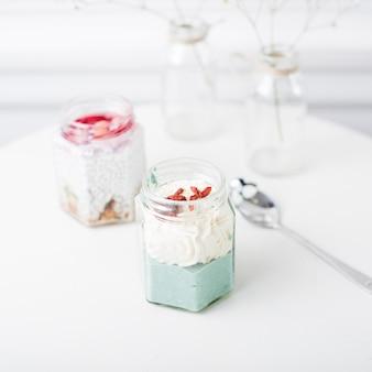 흰색 테이블에 유리 용기에 갓 과일 스무디