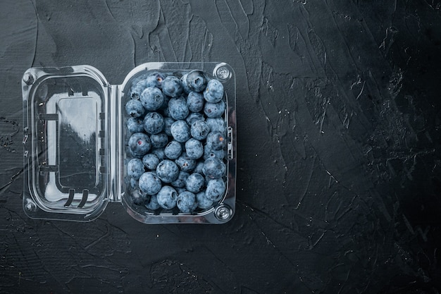 Freshly gathered blueberries, in tray, on black table, top view flat lay