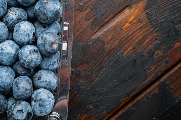 Freshly gathered blueberries in tray on old dark wooden table top view