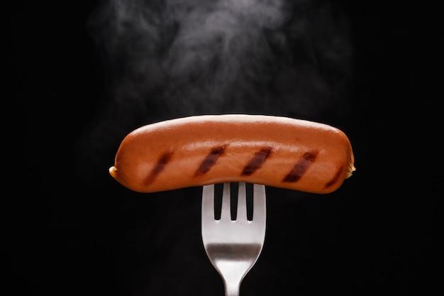 Свежеприготовленная копченая колбаса на серебряной вилке с поднимающимся паром на черном фоне