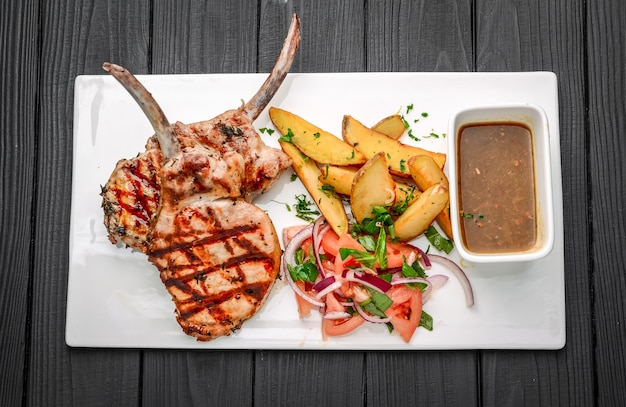 Freshly grilled tomahawk steaks, with fried potatoes, vegetables and sauce