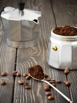 Freshly ground coffee in a spoon, coffee grains are scattered nearby on a brown wooden table