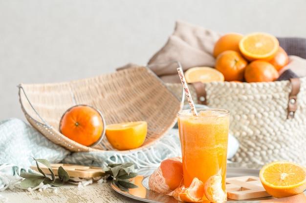 Свежевыжатый органический свежий апельсиновый сок в интерьере дома, с бирюзовым одеялом и корзиной фруктов