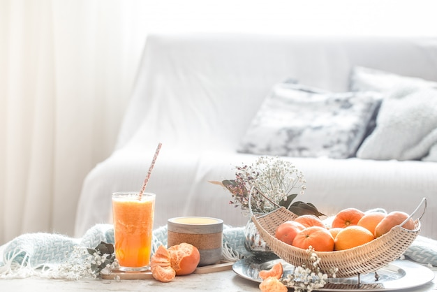 Freshly-grown organic fresh orange juice in the interior of the house, with a turquoise blanket and a basket of fruit