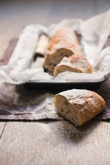 Freshly halved baked bread dusted with flour on wooden table