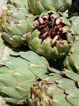 시장에서 갓 수확한 아티초크를 노천 거리 시장에서 판매 중인 야채 더미