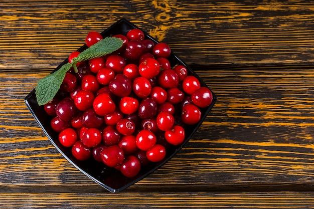 갓 수확한 잘 익은 빨간 체리는 건강한 달콤한 또는 여름 디저트를 위해 그릇에 세척되고 제공되며, 나뭇결 질감이 있는 소박한 나무 배경의 높은 각도 전망