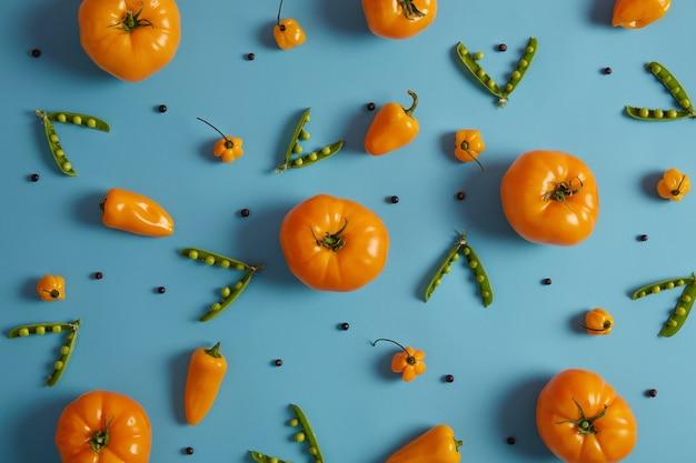 Pomodori, piselli e peperoncino habanero appena raccolti gialli su sfondo blu. verdure mature succose per fare insalata vegana. nutrizione sana e concetto di cibo biologico. vitamine primaverili