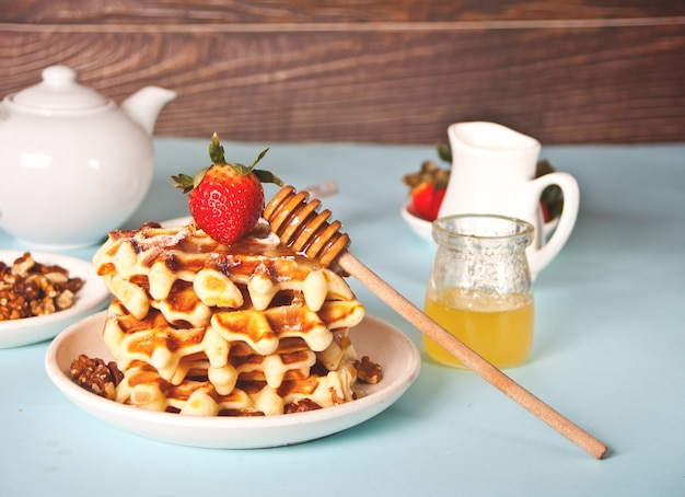 Freshly homemade baked waffles with strawberries and honey.