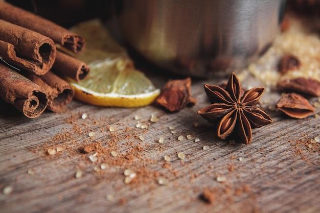 木製のルスリックボードに香りのよい種、柑橘系の果物、レモンを入れたボウルに、作りたての自家製グリューワイン。フラットレイ。テキストの場所。