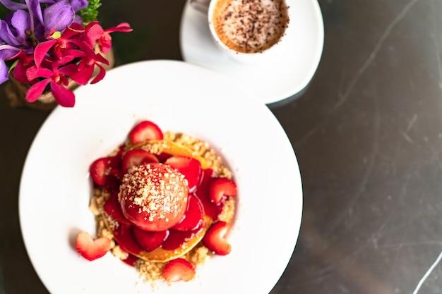 Свежеприготовленные домашние блины с клубникой и крошкой на белой десертной тарелке