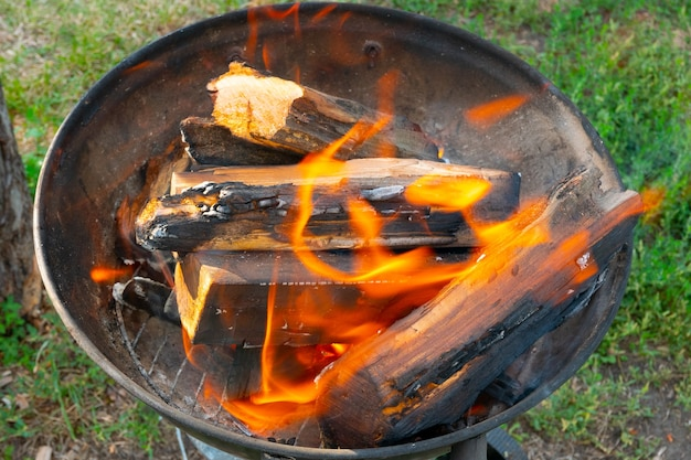 휴대용 바베큐의 작은 조각 위에 불타는 나무 통나무와 함께 갓 켜진 바베큐 불