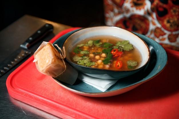 Свежеприготовленный ароматный суп из нута и мяса, посыпанный петрушкой