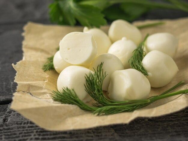 素朴なテーブルの上の包装紙でモッツァレラチーズの作りたてのボール