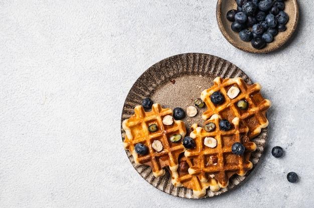 Свежеприготовленные бельгийские вафли с черникой и лесным орехом. вафли с медом и ягодами. место для текста. скопируйте пространство. классический сладкий завтрак