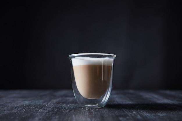 木製のテーブルの上のガラスのカップに泡で作りたてのカプチーノ